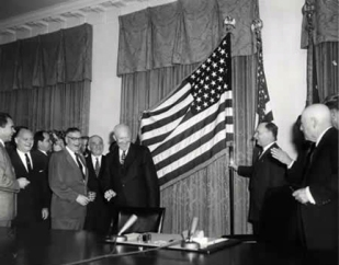 President Eisenhower smiling in front of a new flag of the United States of America, now with a 49th star to represent Alaska. The President is surrounded by a group of government officials.